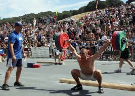 Man snatching at the Crossfit Games watched by an official