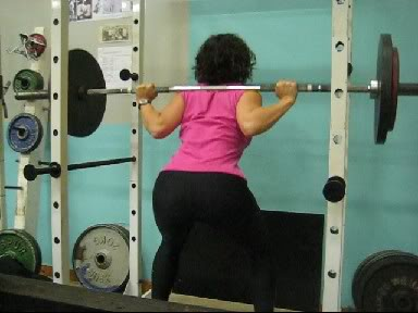 Gubernatric performing barbell back squat in rack